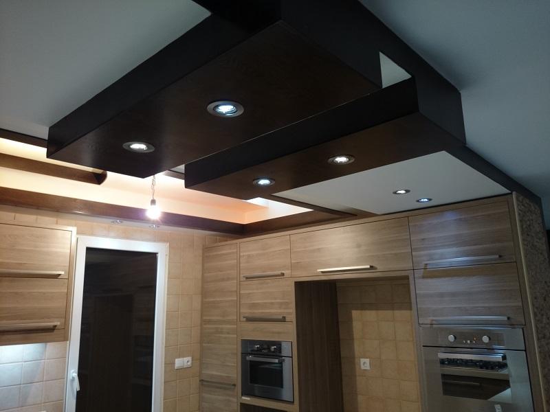 در فضای آشپزخانه از کابینت های مدرن چوبی با کانتر سفید رنگ استفاده شده است